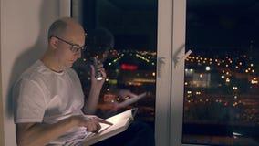 Erwachsener Mann, der auf Fensterbrett- und Lesebuch mit Taschenlampe in der Nacht sitzt stock video footage