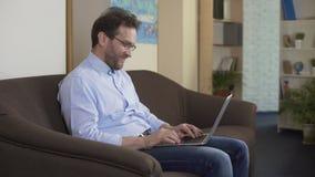 Erwachsener Mann, der auf Sofa- und Grasensozialen netzwerken auf Laptop, Technologien sitzt stock video footage