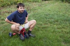 Erwachsener Mann auf einem kleinen Dreirad stockfotografie