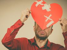 Erwachsener Mann, der defektes Herz hält lizenzfreie stockfotos