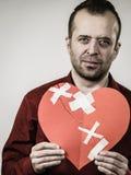 Erwachsener Mann, der defektes Herz hält stockfoto