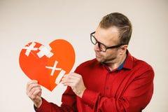 Erwachsener Mann, der defektes Herz hält stockfotografie