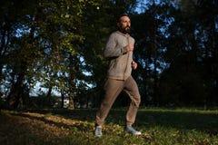 Erwachsener Mann, der in den Park läuft stockfotos