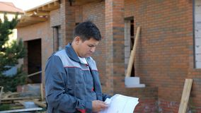 Erwachsener Mann, der die Papierpläne draußen im Bau stehen vom Gebäude betrachtet stock footage