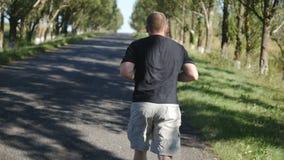 Erwachsener Mann, der draußen in einen Waldweg läuft Alter Mann, der draußen in einer Natur rüttelt stock video
