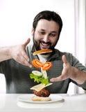 Erwachsener Mann, der einen Burger macht Stockbild