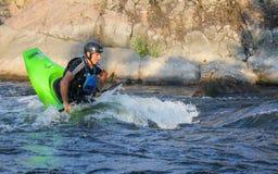 Erwachsener Mann, der einen Kajak auf dem Fluss schaufelt lizenzfreie stockbilder