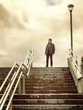 Erwachsener Mann der Einsamkeit, der oben auf der Leiter denkt stockfotografie