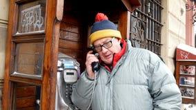 Erwachsener Mann, der emotional am Telefon in einer allgemeinen Telefonzelle an der Straße spricht stock video