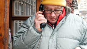 Erwachsener Mann, der emotional am Telefon in einer allgemeinen Telefonzelle an der Straße spricht stock video footage