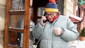 Erwachsener Mann, der emotional am Telefon in einer allgemeinen Telefonzelle an der Straße spricht stock footage