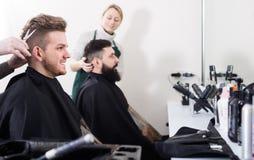 Erwachsener Mann, der ihr Haar von den Friseuren schneiden lässt lizenzfreies stockbild