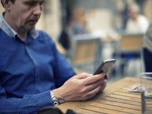 Erwachsener Mann, der Ihren Smartphone in einer Terrasse simst lizenzfreie stockfotografie