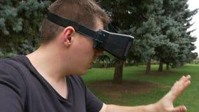 Erwachsener Mann, der im wirklichen Leben um im Freien durch die Linse von VR-Gläsern schaut stock footage