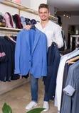 Erwachsener Mann, der Jacke kauft Stockfotos