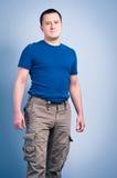 Erwachsener Mann, der mit einem Smirkgesicht steht Stockbild