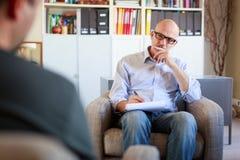 Erwachsener Mann, der mit seinem Psychotherapeuten spricht stockfoto