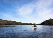 Erwachsener Mann, der norwegischen Fluss im weißen Kajak in Nidelva, Norwegen schaufelt Stockbild