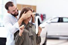 Erwachsener Mann, der der Schönheit im Autosalon Überraschung macht stockfoto