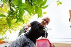 Erwachsener Mann, der in seinem Garten arbeitet lizenzfreies stockbild