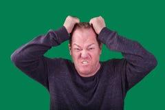 Erwachsener Mann, der seinen Haarwütenden frustrierten Gesichtsausdruck fotografiert auf grünem Schirmhintergrund zieht lizenzfreies stockfoto