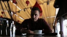 Erwachsener Mann, der Spiel auf dem Smartphone sitzt in der Stange spielt stock footage