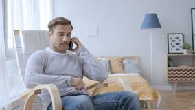 Erwachsener Mann, der am Telefon bei der Entspannung auf Stuhl spricht stock video