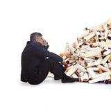 Erwachsener Mann, der vor einem Bündel Zigarettenkippen denkt Stockfotos