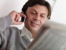Erwachsener Mann, der zu Hause Börsenzulassungen liest lizenzfreie stockfotos