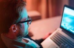Erwachsener Mann, der zu Hause bis zum Nacht auf Laptop-Computer arbeitet stockbilder
