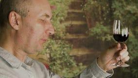 Erwachsener Mann des Porträts, der oben Rotwein vom Glas während des Prüfungsweinabschlusses trinkt Mannshowdaumen up Geste stock video