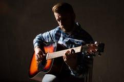 Erwachsener Mann in einem karierten Hemd, das Akustikgitarre spielt Zurückhaltendes Porträt lizenzfreie stockfotos