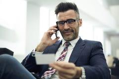 Erwachsener Mann in einer Jacke und in Gläsern, zum von Rechtsdienstleistungen unter Verwendung der Besuchskarte der Firma mit pe lizenzfreie stockbilder