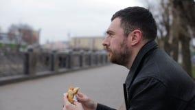 Erwachsener Mann essen Würstchen in der Stadt auf einer Bank stock video footage