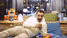 Erwachsener Mann fand einen Kinder-Kasten mit Gold-Mengenkinder-Spielwaren in Kind-` s Raum im Café stock video footage