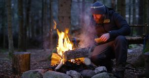 Erwachsener Mann feuert oben das Lagerfeuer ab, das im Wald im Freien ist stock video footage