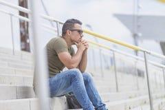 Erwachsener Mann im grünen T-Shirt, das allein auf Treppenaußenseite und t sitzt lizenzfreies stockbild