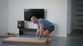 Erwachsener Mann ist, liegend drehend und auf einer großen Pappschachtel des Bodens in einem Raum der Wohnung und schneidet Packb stock video