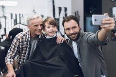 Erwachsener Mann macht selfie auf einem Smartphone mit älteren Männern und Jungen im Friseursalon Stockbild