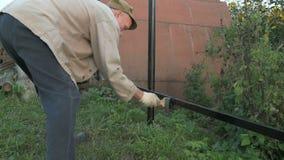 Erwachsener Mann malt den Eisenzaun unter Verwendung der schwarzen Farbe stock video