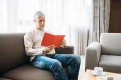 Erwachsener Mann mit dem Notizbuch, das zu Hause auf Couch sitzt stockfoto