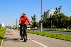 Erwachsener Mann mit dem Rucksack, der Fahrrad in der Stadtstraße fährt Auto stockbild
