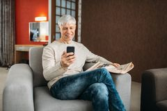 Erwachsener Mann mit dem Telefon, das zu Hause auf Couch sitzt stockfotografie