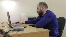 Erwachsener Mann mit einem Bart, der auf Arbeitsplatz am Computer sitzt stock footage