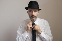 Erwachsener Mann mit Hut und Bart knotet seine Krawatte stockfotografie