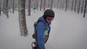 Erwachsener Mann mit rötlichem Bart, der durch Reif auf einem schwarzen Snowboardreiten im Wald des verschneiten Winters hinter i stock footage