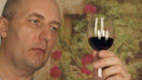 Erwachsener Mann Sommelier, der auf Rotwein im Glas vor schmeckendem nahem hohem schaut stock video