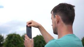 Erwachsener Mann steht am Telefon durch die Videokommunikation in Verbindung und steht auf der Straße HD, 1920x1080 Langsame Bewe stock video