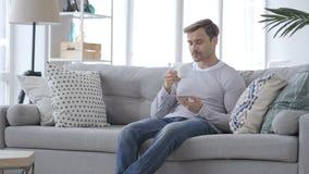 Erwachsener Mann-trinkender Kaffee und Entspannung auf Couch stock video