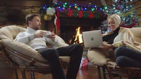 Erwachsener Mann trinkt Kaffee und Gespräche mit seiner glücklichen Frau, die Laptop auf Heiliger Nacht verwendet stock video footage